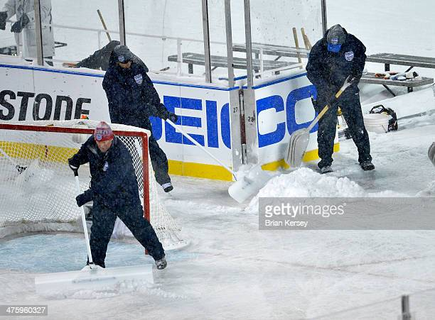 Crews clear snow from the ice during the first period of the 2014 Coors Light NHL Stadium Series game between the Chicago Blackhawks and the...
