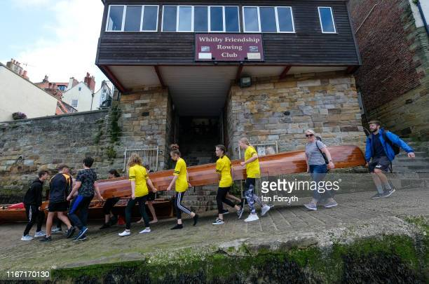 Crews from Scarborough Rowing Club carry their boat to the water during the annual Whitby Regatta on August 10 2019 in Whitby England At over 170...