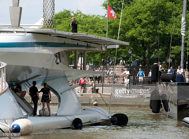 Crews watch as the worlds largest solar boat Switzerlands MS Tûranor PlanetSolar arrives at North Cove marina for a tight fit June 17 2013 in New...