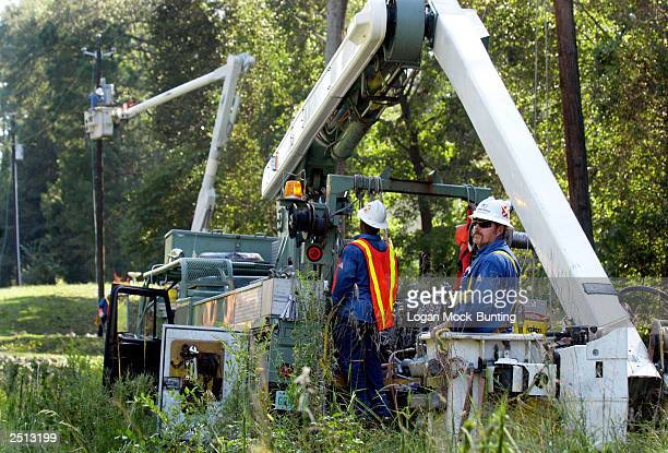 Crews work on downed power lines from Hurricane Isabel's winds September 19 2003 just outside of New Bern North Carolina More than 400000 people...