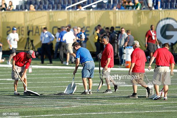 Crews work on the field prior to the NFL Hall of Fame Game between the Green Bay Packers and Indianapolis Colts at Tom Benson Hall of Fame Stadium on...