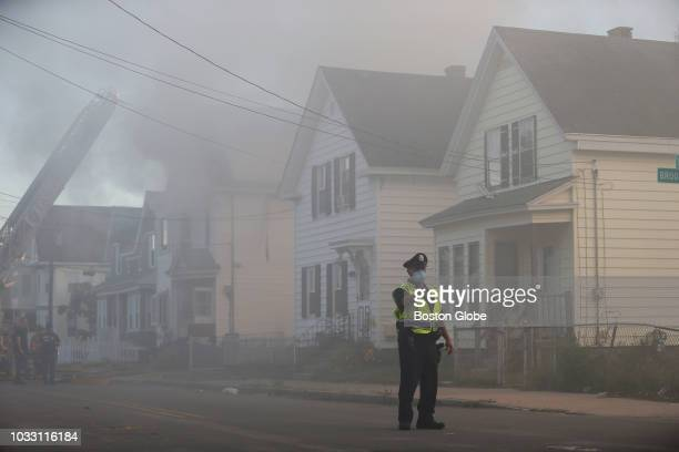 Crews work to knock down a fire as a police officer directs traffic on Bowdoin Street in Lawrence MA on Sep 13 2018 More than 60 fires and at least...