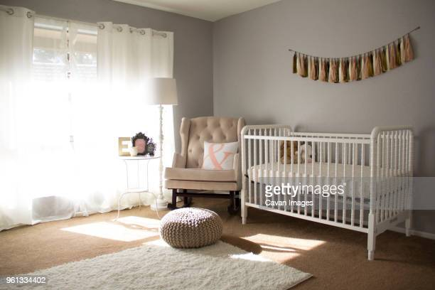 crib by armchair at home - empty crib stock photos and pictures