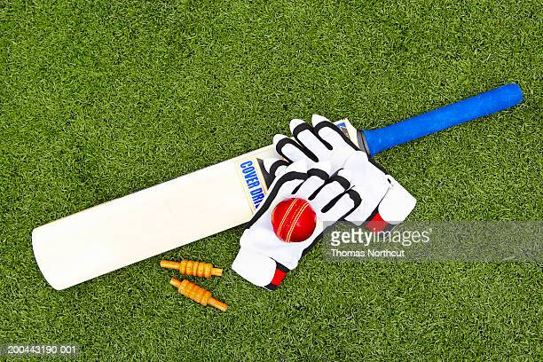 Cricket bails, bat, ball and gloves on artificial turf, elevated view