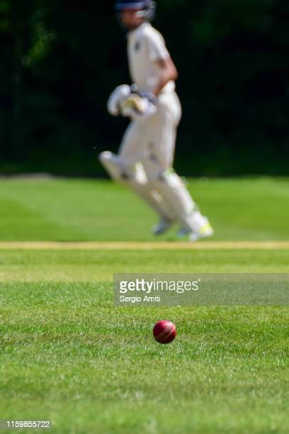 cricket ball with cricket batsman running - cricket ball stock pictures, royalty-free photos & images