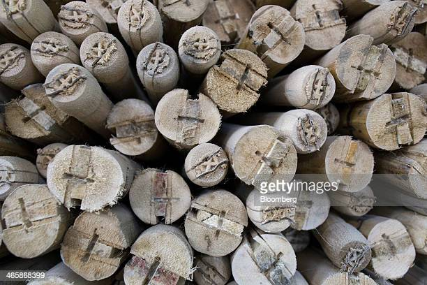 Cricket bat handles sit stacked on shelves at a Stanford Cricket Industries factory in Meerut Uttar Pradesh India on Wednesday Jan 29 2014 The Indian...