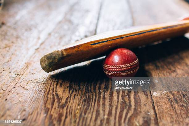 cricket bat resting on ball on wooden floor - sports league stock pictures, royalty-free photos & images