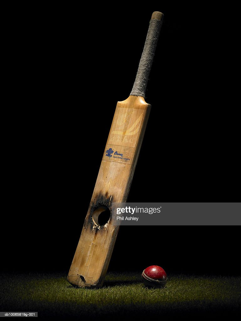 Cricket bat with hole and ball : Stock Photo