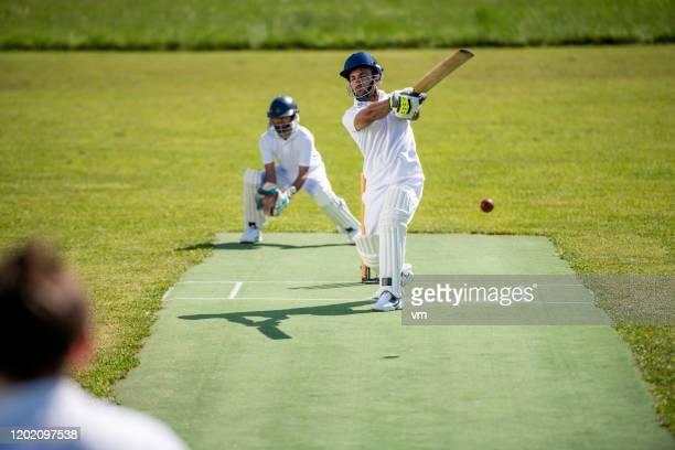 ボールを打った後のクリケットバットマンの瞬間 - バッツマン ストックフォトと画像