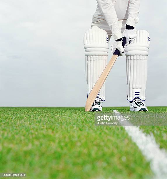 Cricket batsman preparing to bat, low section