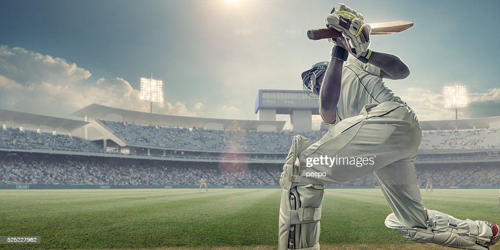 Cricket Batsman With Bat Up After Hitting Ball In Game : Stock Photo
