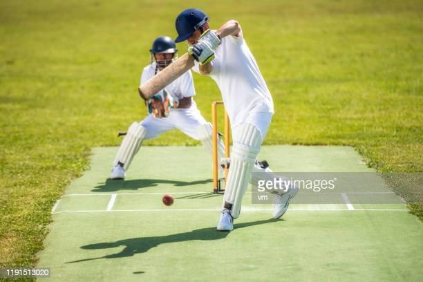 ウィケットキーパーが彼の後ろに立っている間、クリケットバッターはボールを打つ。 - バッツマン ストックフォトと画像