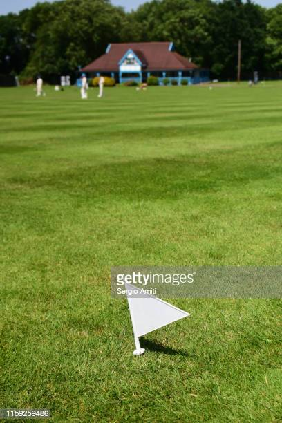 cricket boundary flag and pavilion - cricket pitch stock pictures, royalty-free photos & images