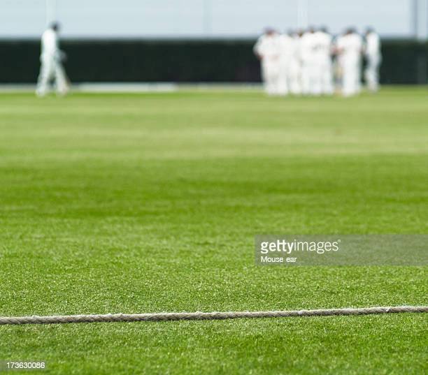 Cricket boundary rope and walking batsman