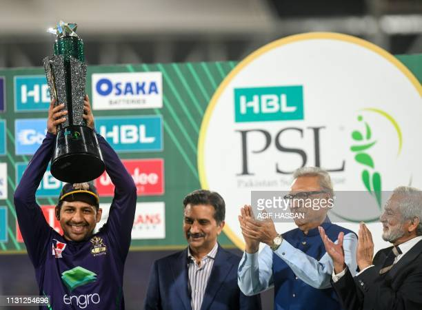 Cricket captain Sarfraz Ahmed of Quetta Gladiators raises the winning trophy next to Pakistan President Arif Alvi and Chairman of the Pakistan...
