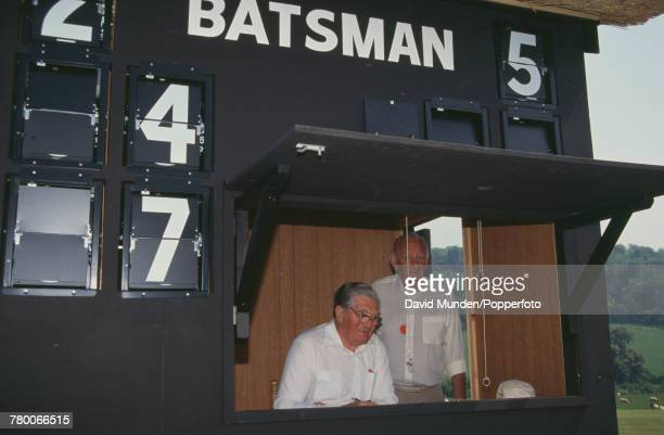 Cricket commentator Brian Johnston helps with the scoring during a charity match between the MCC and Sir Paul Getty's XI at Getty's new cricket...