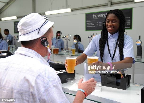 A cricket fan purchases a beer at the Kia Oval