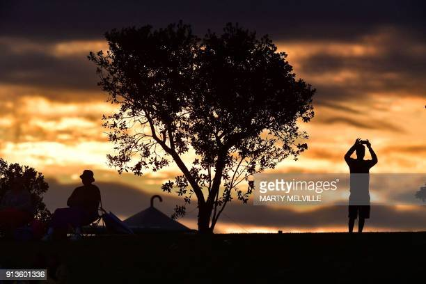 A cricket fan takes a photo at sunset during the U19 cricket World Cup final match between India and Australia at Bay Oval in Mount Maunganui on...