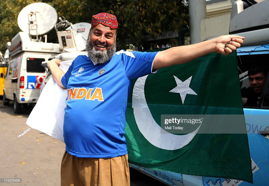 A cricket fan wearing an Indian tshirt and holding Pakistan flag raises friendship slogans outside the PCA cricket stdium in Mohali on Tuesday ahead..