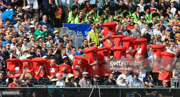 Cricket fans dressed in post box costumes watch play on the second day of the fourth Test match between England and South Africa at Old Trafford...