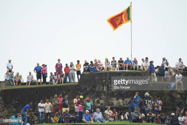 Cricket fans watch from the walls of the Old Fort during Day One of the First Test match between Sri Lanka and England at Galle International Stadium...