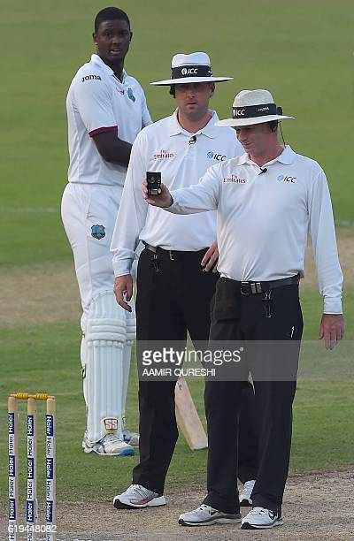 Cricket field umpire Paul Reiffel checks the light on a meter next to another umpire Michael Gough as West Indies' cricket captain Jason Holder looks...