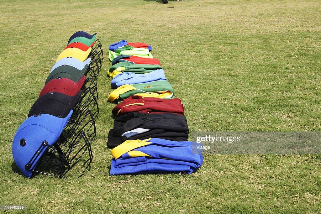 Cricket helmets and jerseys on the ground : Stock Photo