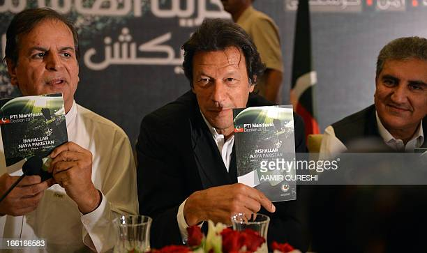 Cricket legend and Chairman of Pakistan TehreekeInsaaf or Movement for Justice party Imran Khan holds a copy of his party manifesto for the...