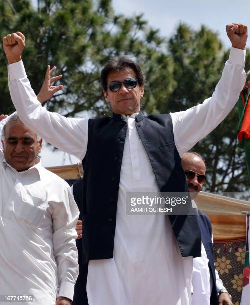 Cricket legend and chairman of Pakistan TehreekeInsaaf or Movement for Justice party Imran Khan gestures as he arrives to address supporters during a...