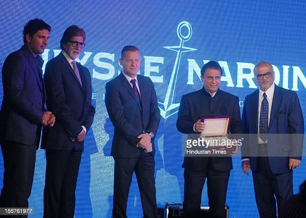 Cricket legend Sunil Gavaskar holding the limited edition Ulysse Nardin watch released in his honur as Yuvraj Singh and Amitabh Bachchan looks attend...