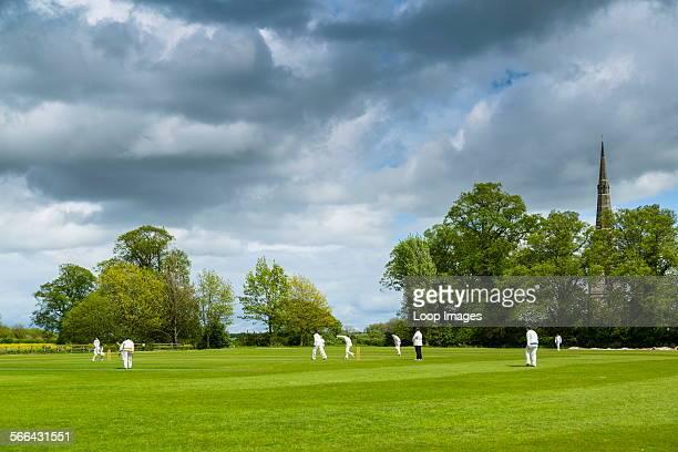 A cricket match on a village field under a stormy spring sky