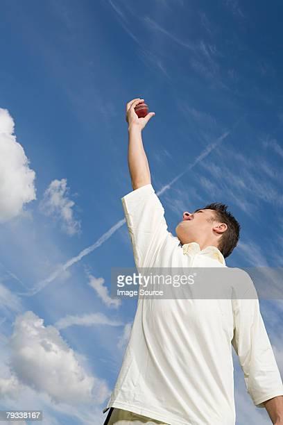 A cricket player catching a cricket ball