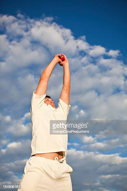 Cricket player catching ball in the air