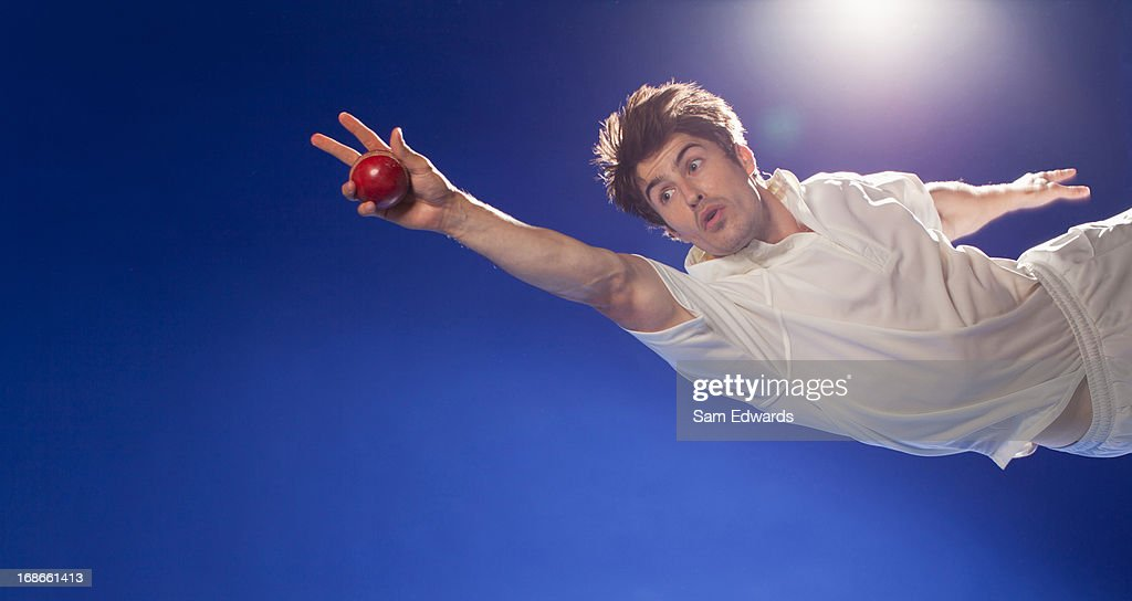 Cricket player catching ball : Stock Photo