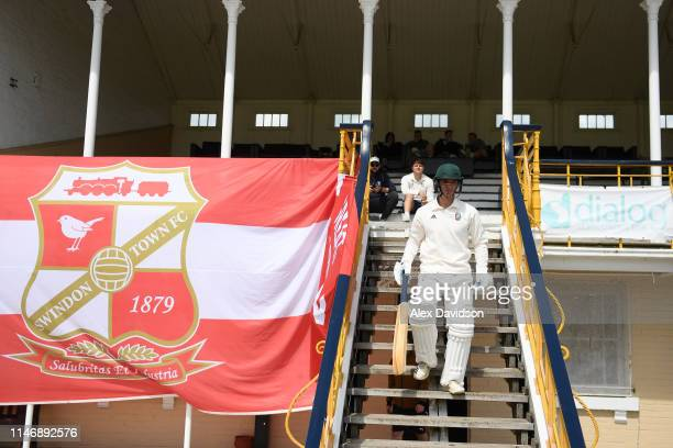 A cricket player of Swindon CC walks out next to a Swindon Town FC flag near the stadium prior to the Sky Bet League Two match between Swindon Town...