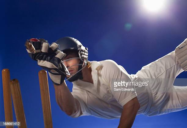 cricket player reaching for bats - cricket player stock pictures, royalty-free photos & images