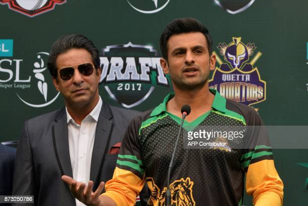 Cricket player Shoaib Malik speaks as former Pakistani cricket captain Wasim Akram looks on during the third edition of the Pakistan Super League...