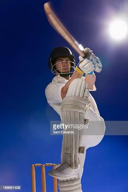 Cricket player swinging bat