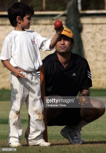 Cricket SACHIN TENDULKAR KEEPS A SHARP VIGIL ON HIS SON ARJUN'S GRIP DURING HIS NET PRACTICE AT MIG ON TUESDAY