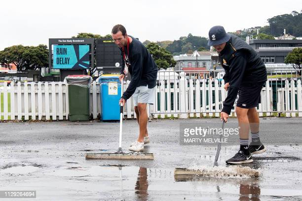 Cricket staff remove water from the public area during a rain delay on day two of the 2nd Test cricket match between New Zealand and Bangladesh at...