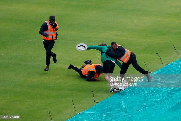 A cricket supporter is stopped by security staff after they invaded the pitch shortly before the game was called off due to rain during the third day...