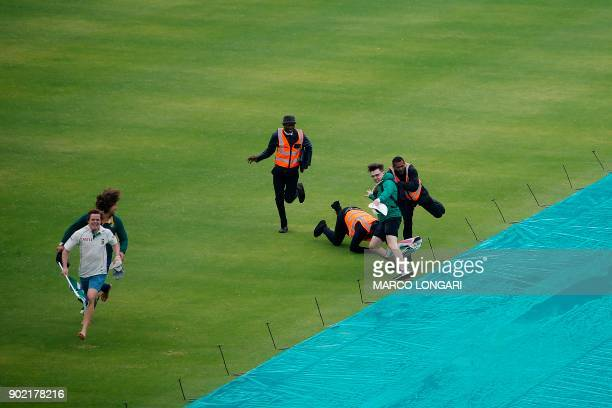 Cricket supporters are stopped by security staff after they invaded the pitch shortly before the game was called off due to rain during the third day...