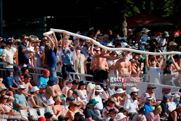 Cricket supporters holds empty plastic cups that beer is served in to form a snake during the second day of the second Test cricket match between...