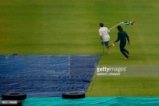 Cricket supporters invade the pitch shortly before the game was called off due to rain during the third day of the first Test cricket match between...