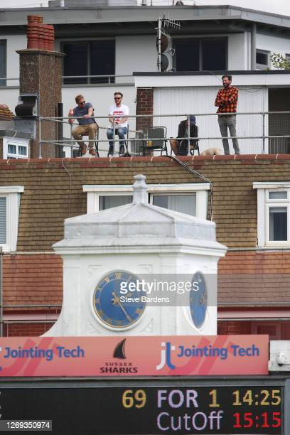 Cricket supporters watch from the balcony of a flat during the T20 Blast match between Sussex Sharks and Surrey at The 1st Central County Ground on...