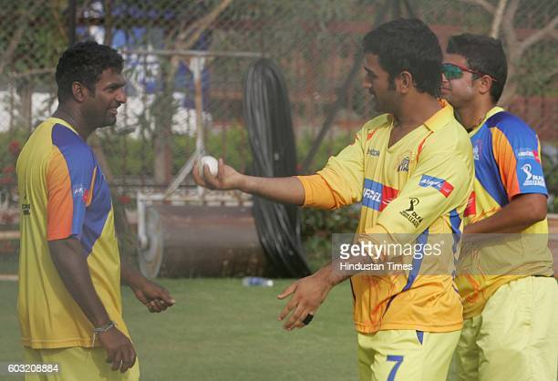Cricket Team Chennai's captain MS Dhoni chats with bowler Muttiah Muralidharan during the net practice session on the eve of their match against Team...