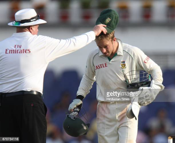Cricket Umpire puts cap back on South africa wicketkeeper Ab DeVilliers during the third day of the first test match between India and South Africa...