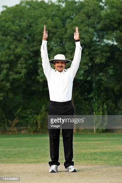 Cricket umpire signaling six