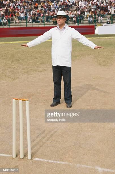 Cricket umpire signaling Wide Ball