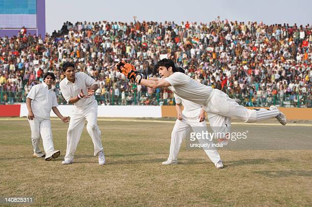 Cricket wicket keeper and fielders attempting for a catch